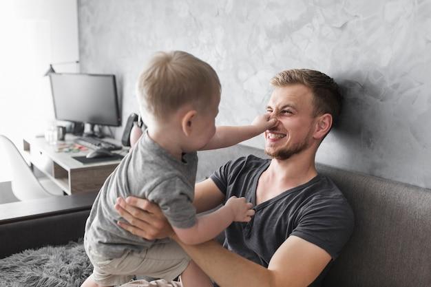 Close-up van zoon die de neus van zijn vader houdt terwijl het spelen met hem