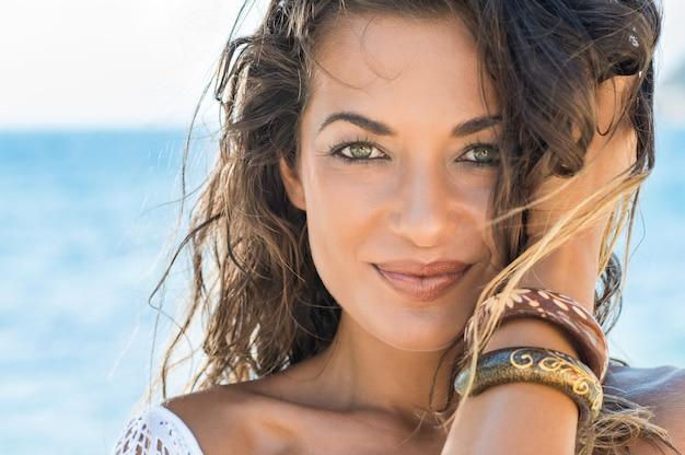 Close-up van zorgeloos meisje kijken camera op tropisch strand