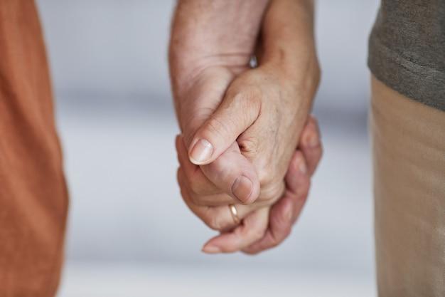 Close up van zorgzaam senior paar hand in hand en samen wandelen, kopieer ruimte