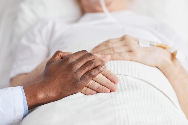 Close up van zorgzame afro-amerikaanse arts hand in hand met senior patiënt liggend in ziekenhuisbed, kopieer ruimte