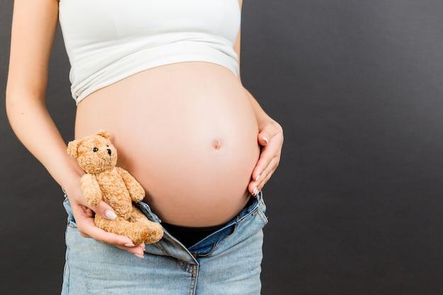 Close up van zwangere vrouw in uitgepakte jeans omarmen teddybeer in de buurt van haar buik