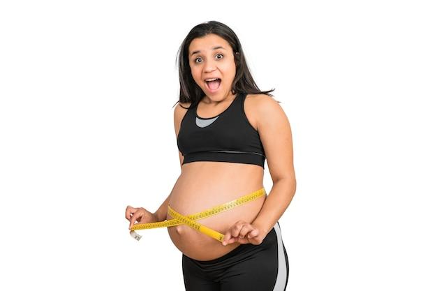 Close-up van zwangere vrouw met behulp van meetlint om de ontwikkeling van de baby te controleren