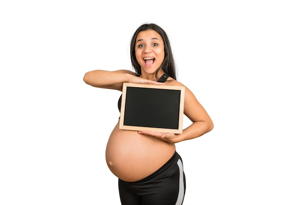 Close-up van zwangere vrouwenholding en iets op bord tonen. advertentieconcept voor zwangerschap, moederschap en promotie.