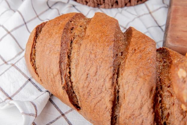 Close-up van zwart brood op geruite doek