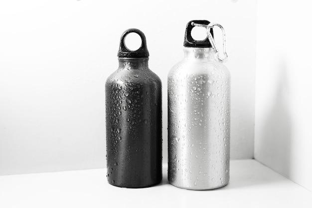 Close-up van zwart en zilver, herbruikbare aluminium thermo fles bespoten met water, geïsoleerd op een witte achtergrond.