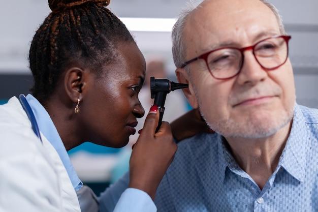 Close up van zwarte arts met behulp van otoscoop voor oor checkup