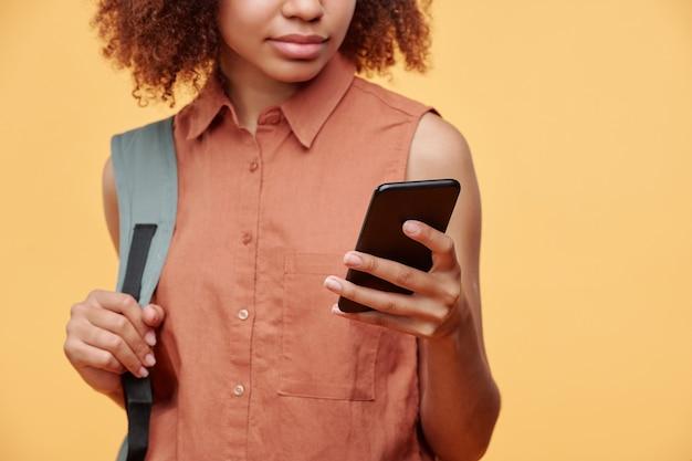 Close-up van zwarte de holdingsriem van de studentenmeisje van de schooltas en het scrollen van sociale media op smartphone tegen gele achtergrond