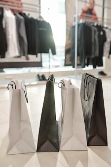 Close-up van zwarte en witte boodschappentassen die op vloer in moderne kledingwinkel worden geplaatst