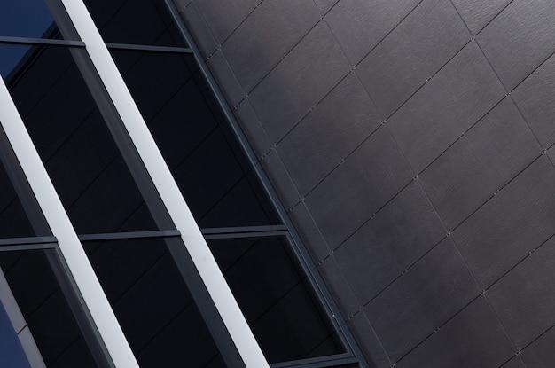 Close-up van zwarte glazen wand en zwarte muur bedekt met unsmooth tegels