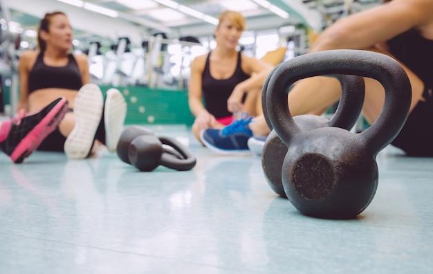 Close-up van zwarte ijzeren kettlebell en mensengroep zittend op de vloer van een fitnesscentrum