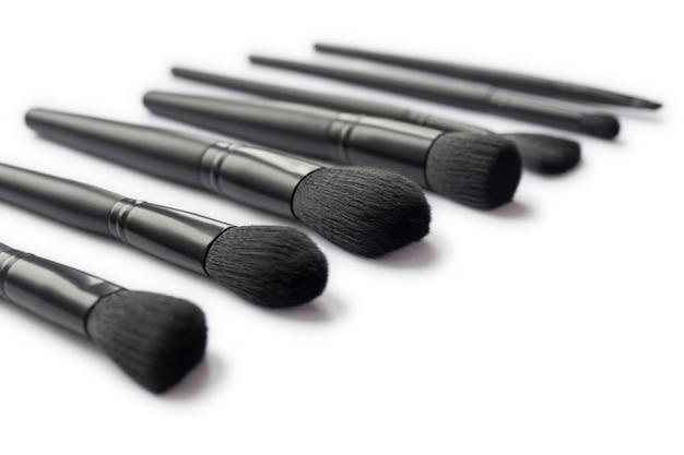 Close-up van zwarte make-upborstels die op witte ruimte worden geïsoleerd