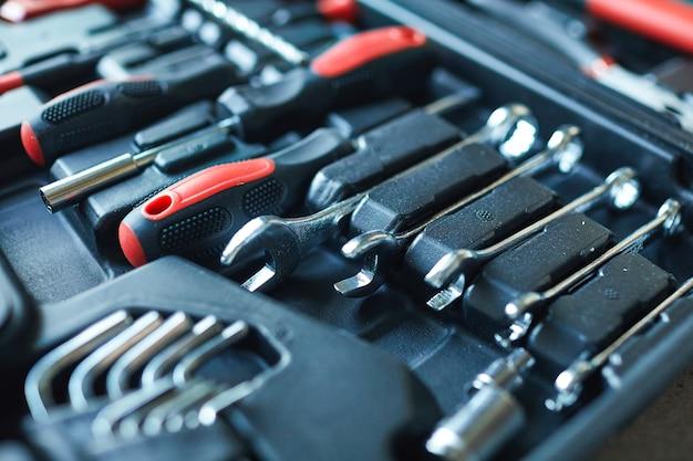 Close up van zwarte open gereedschapskist met set moersleutels en schroevendraaier op bouwplaats, kopieer ruimte