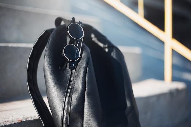 Close-up van zwarte rugzak en ronde zonnebril op stedelijke trappen.