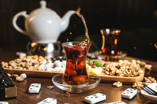 Close-up van zwarte thee in armudu glas met verschillende zoetigheden op tafel