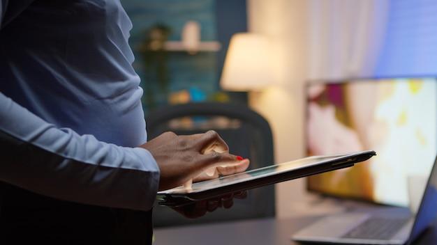 Close-up van zwarte vrouw die tablet gebruikt, bladert, erop typt, 's avonds laat in de woonkamer staat en pauze neemt. afrikaanse freelancer met behulp van moderne technologienetwerken die overuren maken