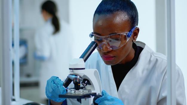 Close up van zwarte vrouw op zoek in microscoop in modern uitgerust lab. multi-etnisch team onderzoekt virusevolutie met behulp van hightech voor wetenschappelijk onderzoek naar behandelingsontwikkeling tegen covid19