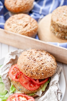 Close-up veggie quinoaburger met tomaat, ui en hamburgerbrood