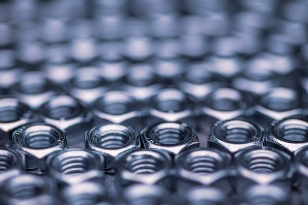 Close-up verchroomde metalen moeren in de vorm van honingraten liggen naast elkaar en vormen een gebied. reparatie- en reserveonderdelenconcept