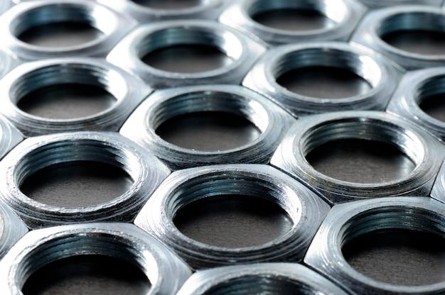 Close-up verchroomde metalen moeren in de vorm van honingraten liggen naast elkaar en vormen een gebied.