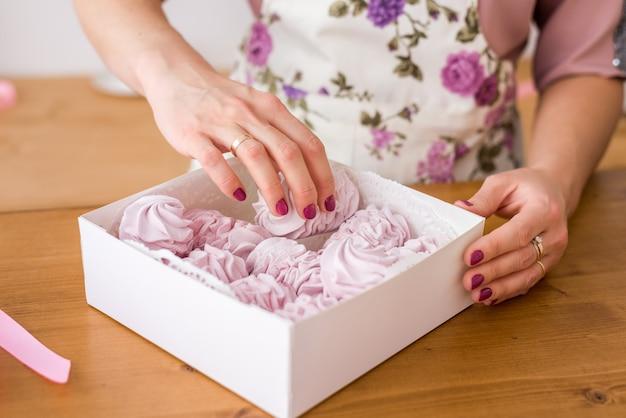 Close-up verpakking van zelfgemaakte marshmallows. dames handen met een marshmallow geschenkdoos