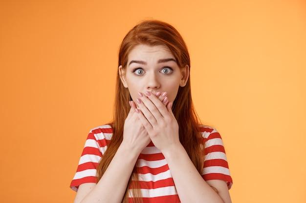 Close-up verrast geschokt rood meisje staren camera sprakeloos mond gesloten handpalmen verbaasd erg indrukwekkend...