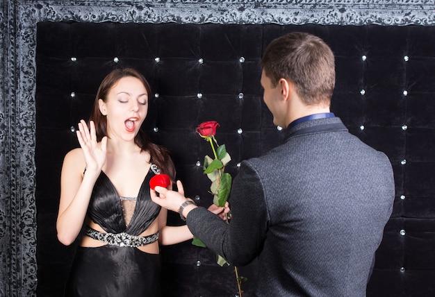 Close-up verrast vriendinnetje kreeg een rode rozenbloem en een rood juwelendoosje met ring van zijn vriendje.