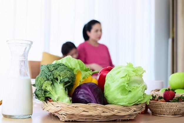 Close-up verse groente in geweven mand, gezet op houten bureau vooraan vage vrouw en haar jong geitje