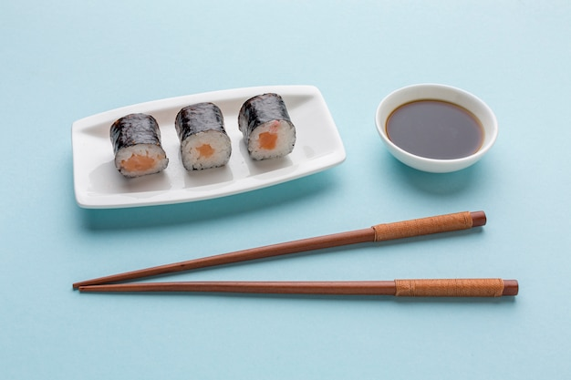 Close-up verse sushi rolt met stokjes en sojasaus