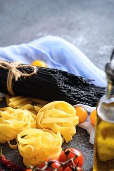 Close-up verticaal beeld van italiaanse voedselingrediënten, deegwaren, zwarte spaghetti, tomaten, olijfolie op grijze achtergrond, dinerconcept koken