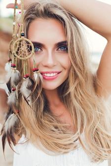 Close-up verticaal portret van vrij blond meisje met lang haar op strand. ze houdt versieringen met veren in de hand en lacht naar de camera.