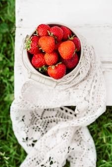 Close-up verticale aardbeien in een emmer, zomer in het dorp, oogst.