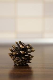 Close-up verticale shot van een dennenappel op een houten tafel