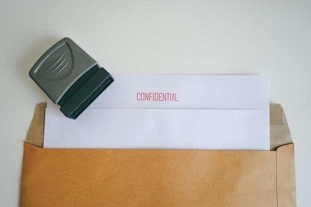 Close-up vertrouwelijk document met bruine tas en vertrouwelijke stempel.