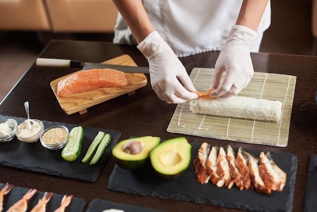 Close-up viev van chef-kokhanden die japans voedsel voorbereiden