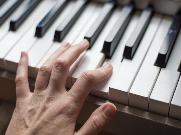 Close-up vingers van pianist op de pianotoetsen, armen speelt solo van muziek of nieuwe melodie. handen van mannelijke muzikant spelen op synthesizer.