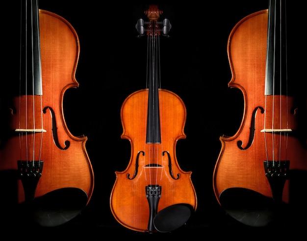 Close-up vioolorkest muzikale instrumenten op zwarte achtergrond