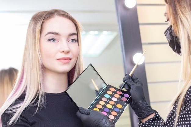 Close-up visagist brengt make-up op de ogen van het meisje. oogschaduw, palet. schoonheidssalon.
