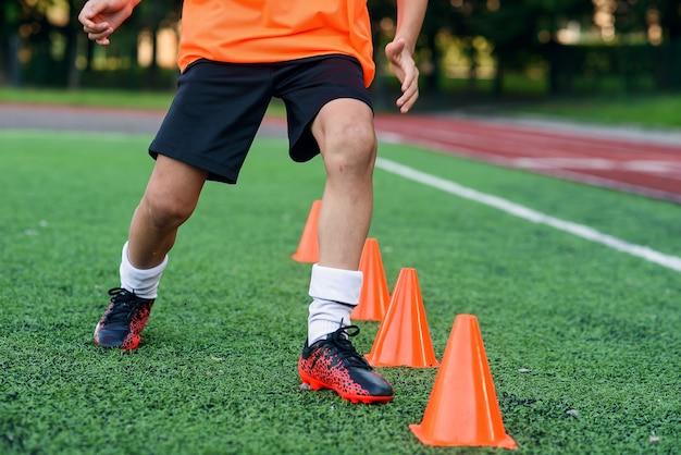 Close-up voetballers die onder plastic oranje kegels lopen