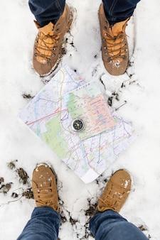 Close-up voeten met kaarten en sneeuw