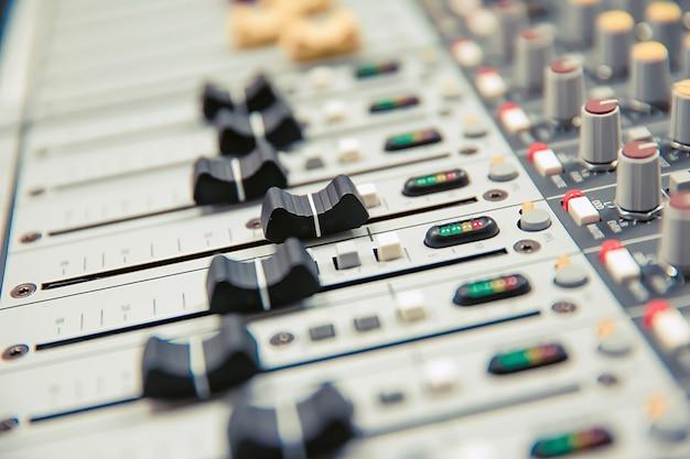 Close-up volumeschuif van digitale geluidsmixer in de studio.