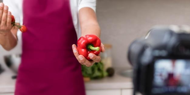 Close-up volwassen mannetje dat groene paprika op camera voorstelt