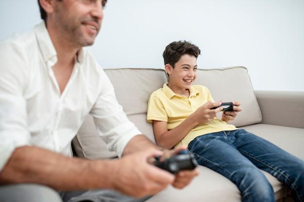 Close-up volwassene en kind spelen met controllers
