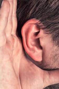 Close-up voor hand op oor