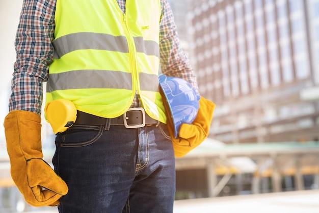 Close-up vooraanzicht engineering mannelijke bouwvakker stand blauwe veiligheidshelm te houden en handschoenen met reflecterende kleding te dragen