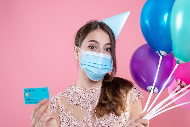 Close-up vooraanzicht schattig feestmeisje met medische masker met ballonnen en kaart