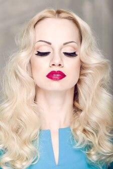 Close-up voorportret van een blonde jonge vrouw met krullend haar en avondsamenstelling, met gesloten ogen.