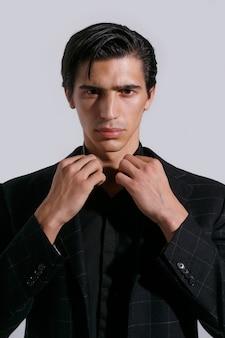 Close-up voorportret van een zelfverzekerde knappe jongeman in zwarte kleding op witte achtergrond. verticale weergave.