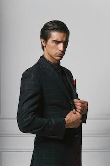 Close-up voorportret van een zelfverzekerde zakenman in zwart pak met rode zijden sjaal in zak, over grijze achtergrond.