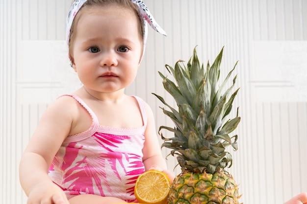 Close-up voorportret van jong klein babymeisje in overhemd met roze tropisch patroon