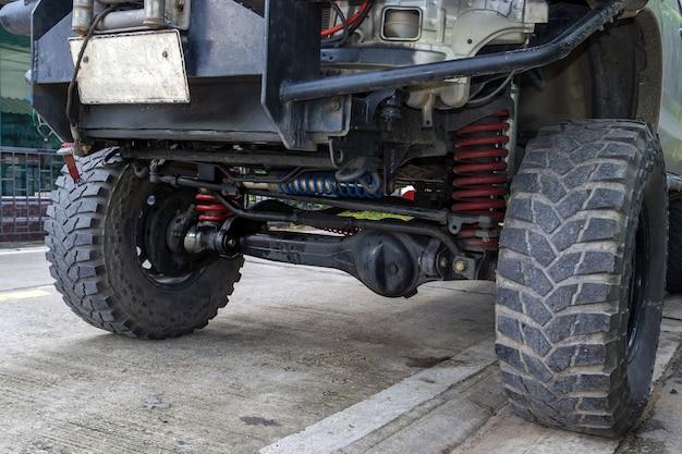 Close-up voorwiel en ophanging van de vierwielaangedreven pick-uptruck.